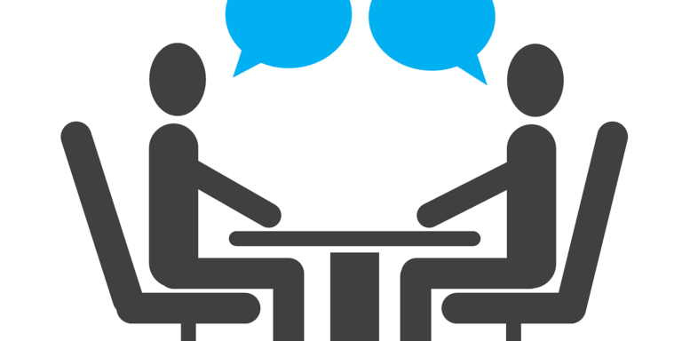 Two people sitting across a desk from each other with blue speech bubbles
