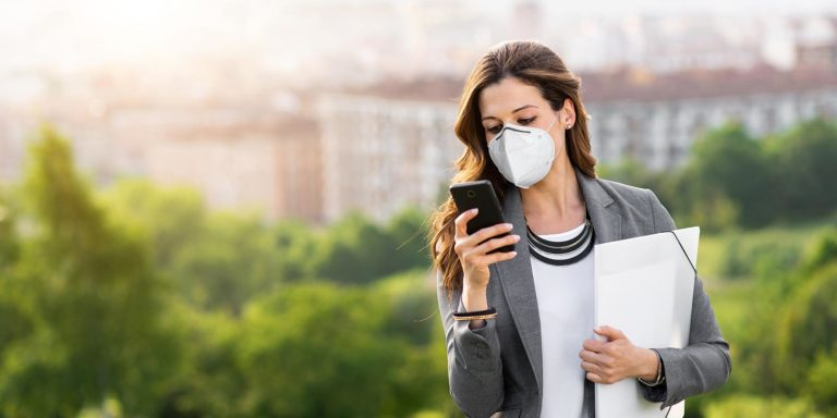 A women wearing a mask holding a folder and checking here cell phone