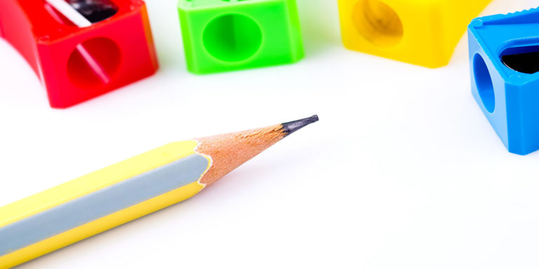 A wooden pencil and 4 different colored manual pencil sharpeners