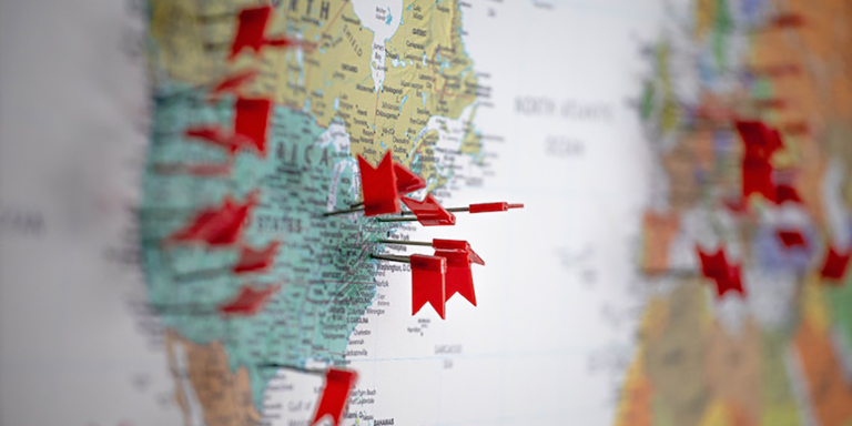 Map of North America with red thumbtacks marking client locations to determine sales territory breakdown