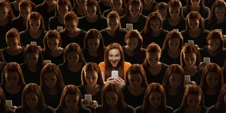 A large group of women all looking at their phones, with a spotlight on one in the middle.